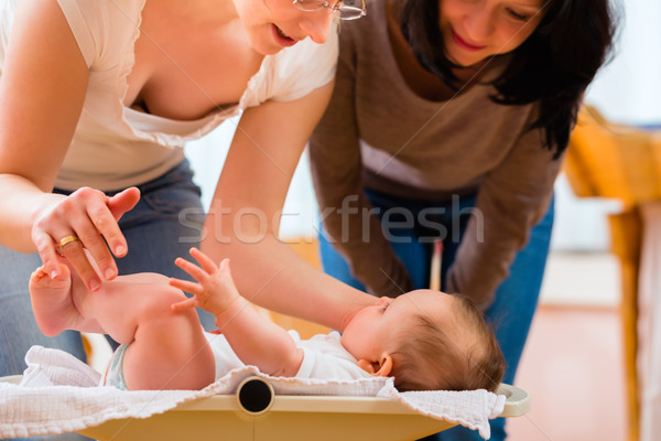 Midwife measuring weight or newborn baby Stock photo © Kzenon