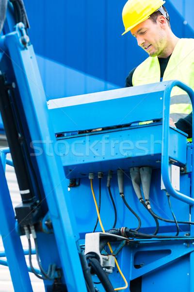 Crane driver driving hydraulic lifting ramp with control desk Stock photo © Kzenon