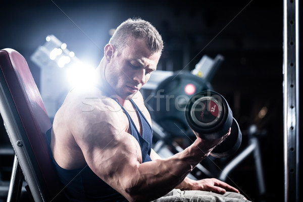 Man at fitness training with dumbbells in gym Stock photo © Kzenon
