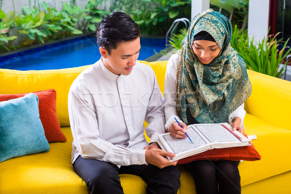 Asian Muslim couple reading together Koran or Quran  Stock photo © Kzenon
