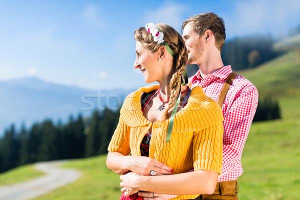 Couple in Tracht on Alp mountain summit at vacation Stock photo © Kzenon