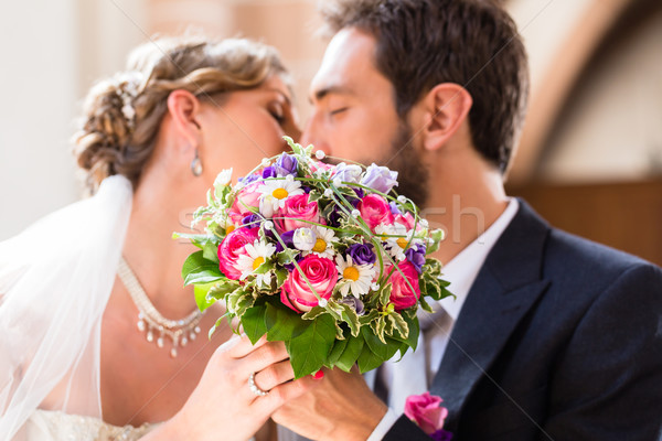 Bridal couple giving kiss in church at wedding Stock photo © Kzenon
