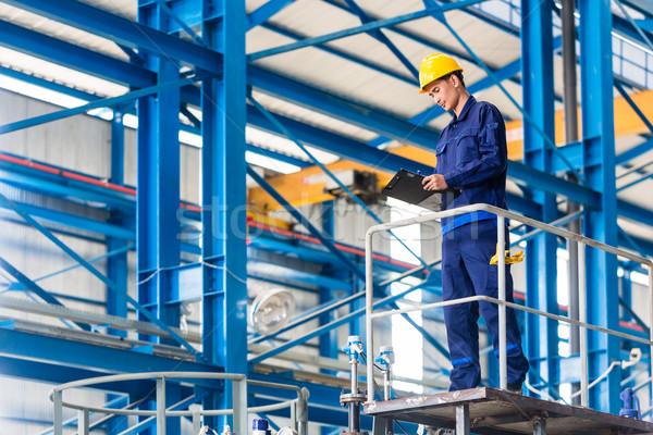 Worker in large metal workshop checking work Stock photo © Kzenon