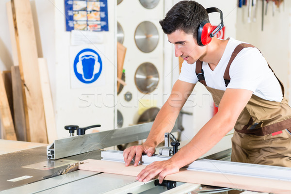 Carpenter cutting wooden plank in his workshop Stock photo © Kzenon