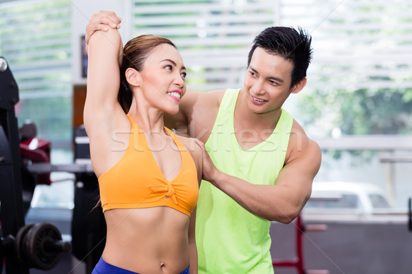 Asian man helping girl stretching and warming up in gym  Stock photo © Kzenon