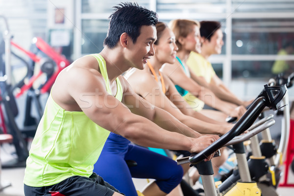 Young Asian athletes side by side in spinning class Stock photo © Kzenon