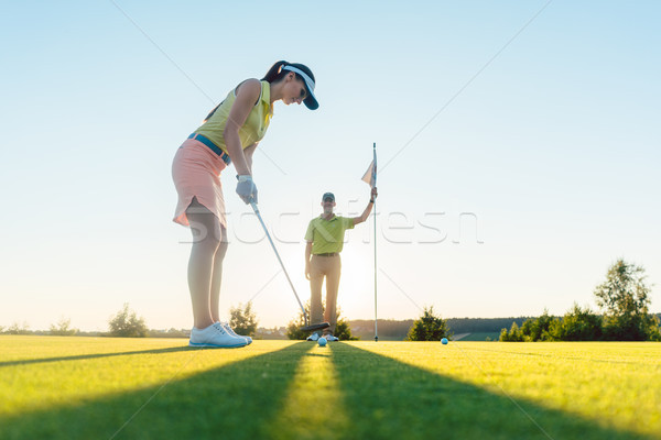 Fit woman exercising hitting technique during golf class with an Stock photo © Kzenon