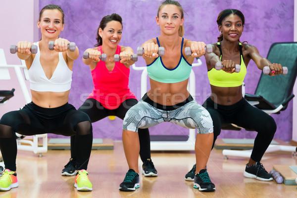 women doing squats holding dumbbells at functional training grou Stock photo © Kzenon