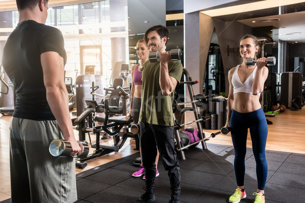 Three young people smiling while alternating dumbbell bicep curl Stock photo © Kzenon