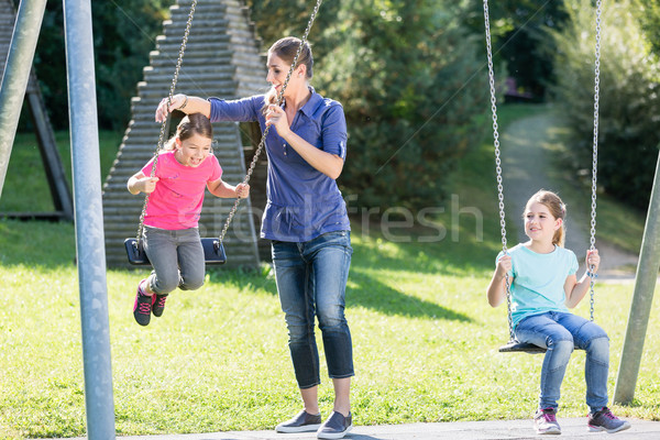 Family with two girls and mother on playground swing Stock photo © Kzenon