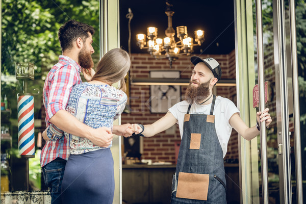 Cool hairstylist giving a fist bump to a happy customer at the door of a salon Stock photo © Kzenon