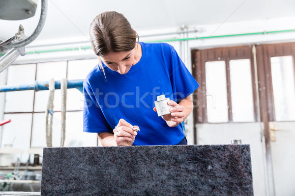 Female Stonemason applying inscription on tombstone Stock photo © Kzenon