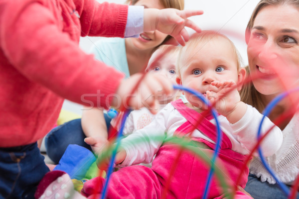 Group of happy young mothers watching their cute and healthy babies play Stock photo © Kzenon