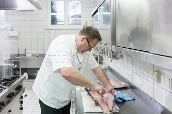 Chef in restaurant kitchen filleting carp fish Stock photo © Kzenon