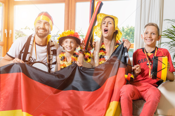 Whole family cheering for the German soccer team in front of TV Stock photo © Kzenon