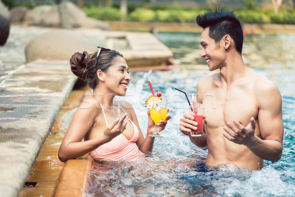 Young man flirting with an attractive woman in a trendy swimming pool Stock photo © Kzenon