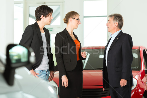 Mature man with young couple and autos in car dealership Stock photo © Kzenon