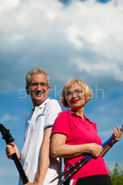 Happy mature or senior couple doing Nordic walking in summer Stock photo © Kzenon