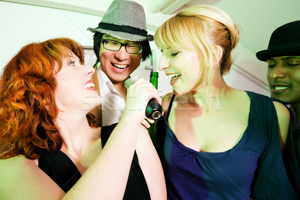 Group of friends at karaoke party Stock photo © Kzenon