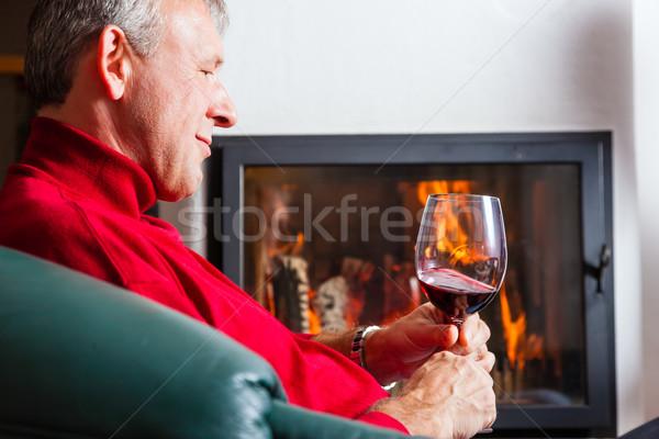 Férfi iszik vörösbor kandalló érett férfi pohár Stock fotó © Kzenon