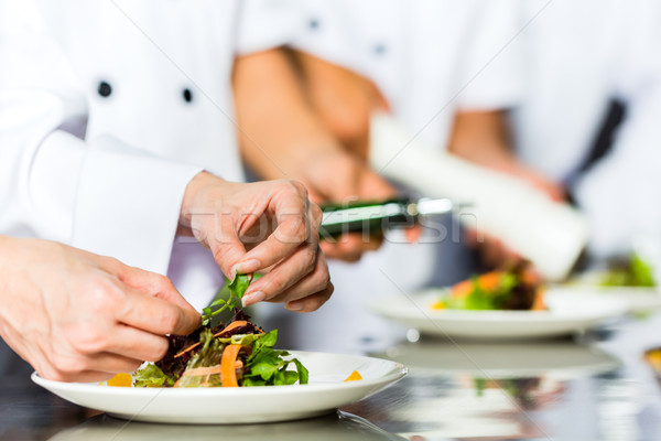 Chef in restaurant kitchen cooking Stock photo © Kzenon