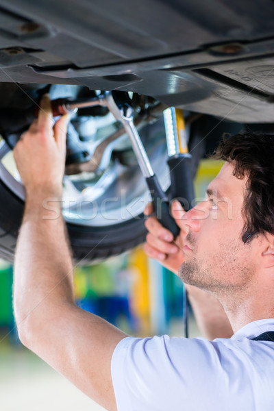 Stock photo: Mechanic working in car workshop on wheel