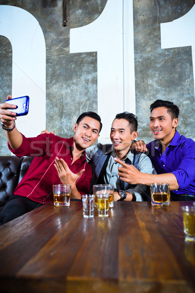 Asian friends taking pictures or selfies in fancy night club Stock photo © Kzenon