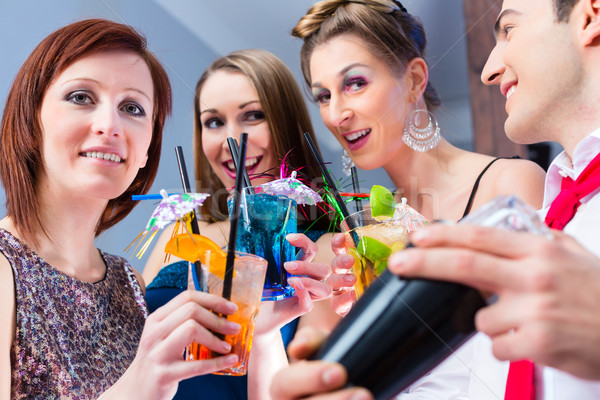 Friends celebrating with barkeeper in cocktail bar Stock photo © Kzenon