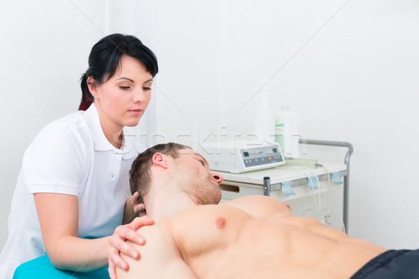Physiotherapist set patient in practice   Stock photo © Kzenon