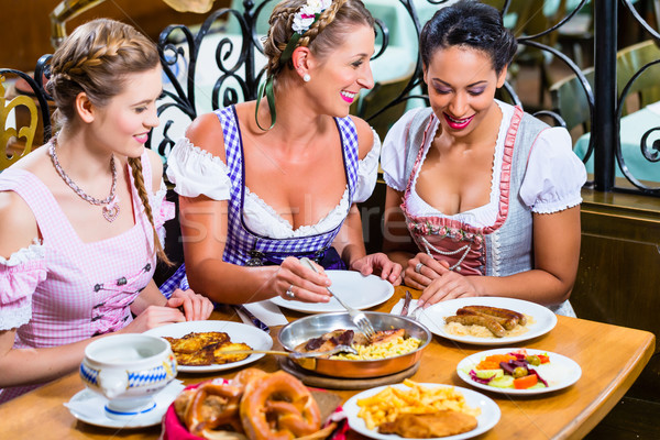 Women in Bavarian pub eating food for dinner Stock photo © Kzenon