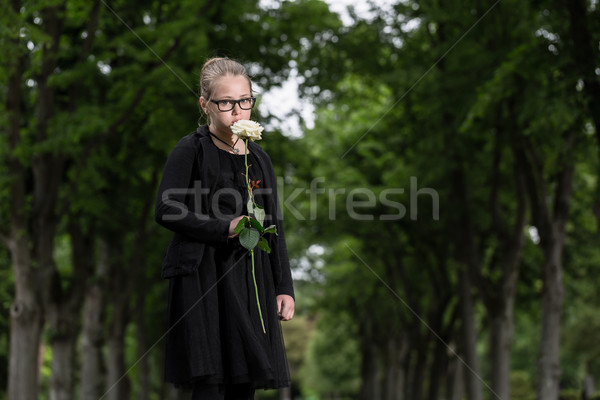 girl with white rose mourning deceased on graveyard Stock photo © Kzenon