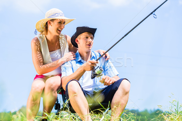 Man with fishing rod angling at lake enjoying hug  Stock photo © Kzenon