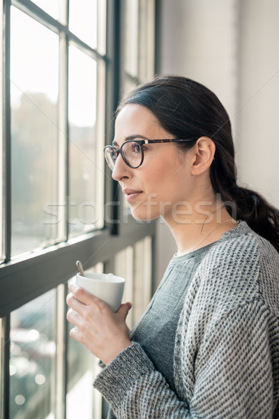 Young pensive woman looking through the window during break  Stock photo © Kzenon