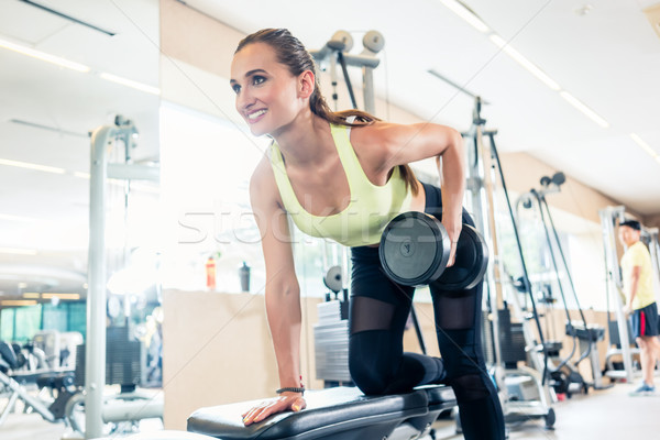 Low-angle view portrait of a beautiful fit woman smiling while exercising Stock photo © Kzenon