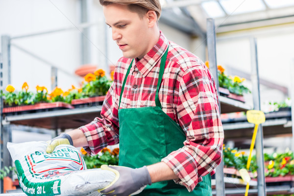 Young man during work at the flower market Stock photo © Kzenon