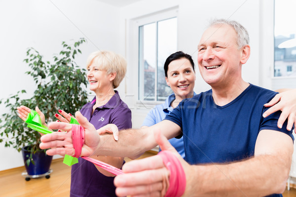 Physio showing senior couple how to use rubber band as expander Stock photo © Kzenon
