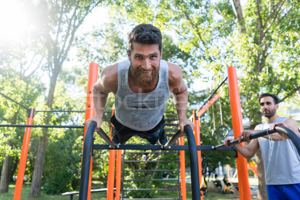 Athletic young man doing push-ups during outdoor workout in a fitness park Stock photo © Kzenon