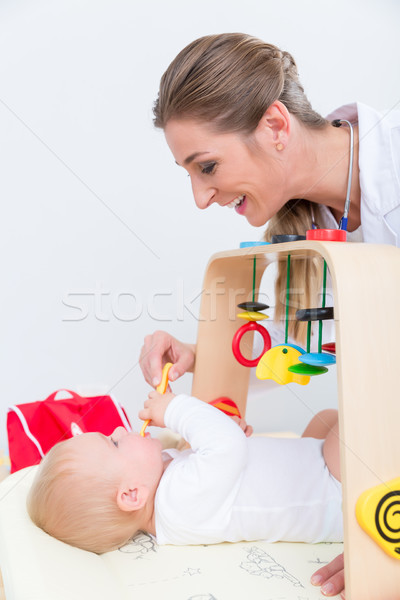 Dedicated pediatrician playing with a healthy and active baby Stock photo © Kzenon