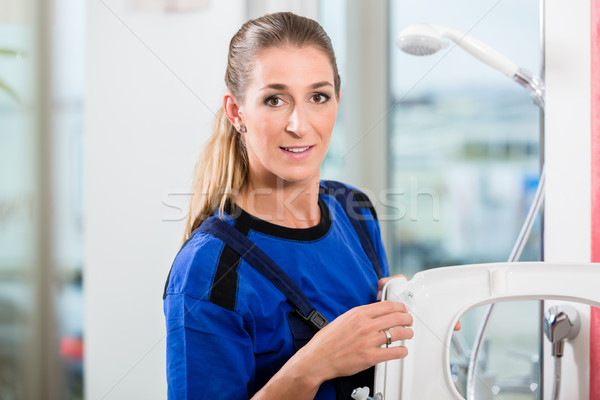 Female maintenance worker checking the quality of a toilet seat  Stock photo © Kzenon