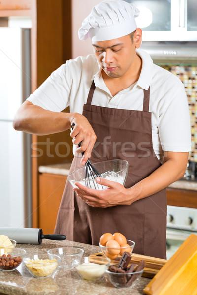 Asian man baking cake in home kitchen Stock photo © Kzenon