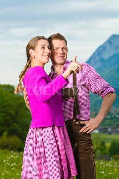 Happy couple in Alpine meadow in Tracht Stock photo © Kzenon