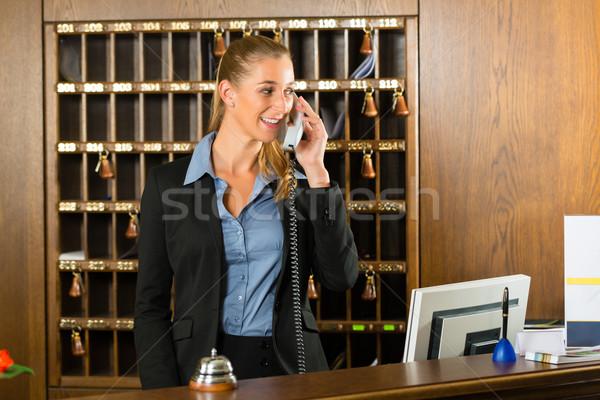 Reception of hotel - desk clerk taking a call Stock photo © Kzenon