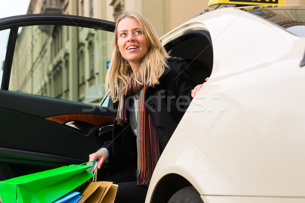 Young woman gets out of taxi Stock photo © Kzenon