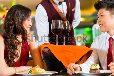 Stock photo: Waiter serving Chinese couple red wine in fancy restaurant