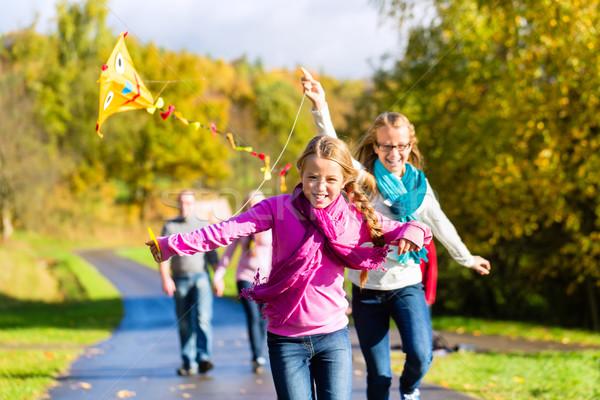 Family take walk in autumn forest flying kite Stock photo © Kzenon