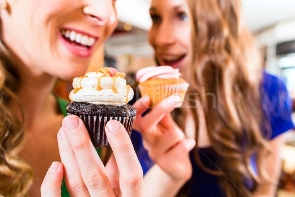 Women eating muffins while coffee drinking Stock photo © Kzenon