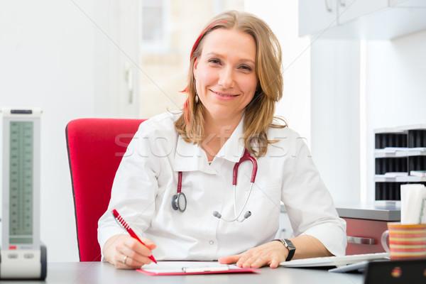 Doctor writing medical prescription in surgery Stock photo © Kzenon