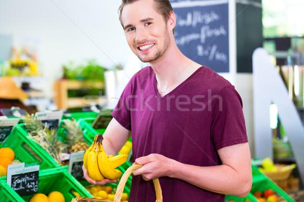 Man selecting fruits in corner shop Stock photo © Kzenon