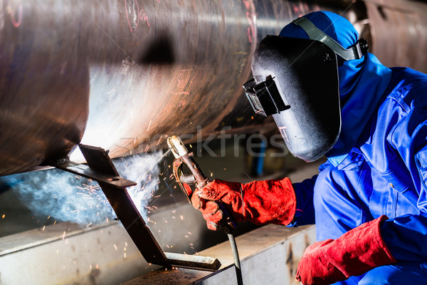 Welder in factory welding metal pipes Stock photo © Kzenon