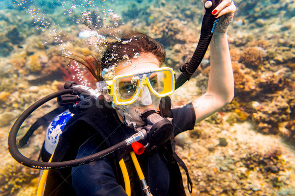 Woman in vacation scuba diving to tropical coral reef Stock photo © Kzenon